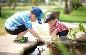 Two kindergarten kids friends holding hands playing at park