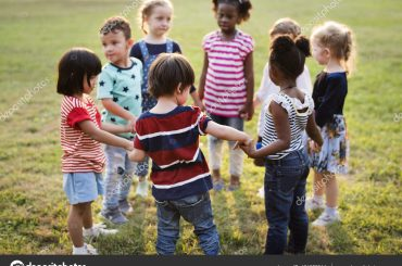Group of kindergarten kids friends holding hands playing at park